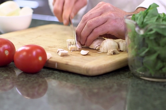 Hand chopping vegetables on cutting board